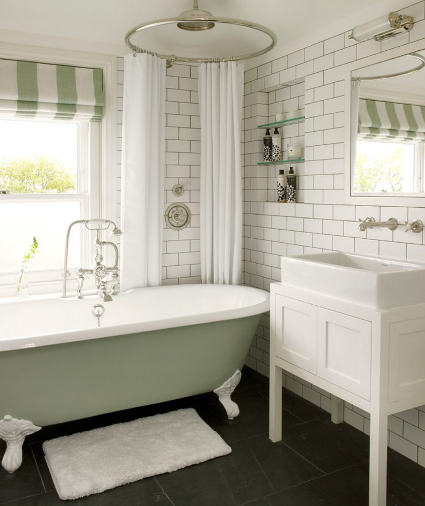 Traditional clawfoot tub in a bathroom with subway tile