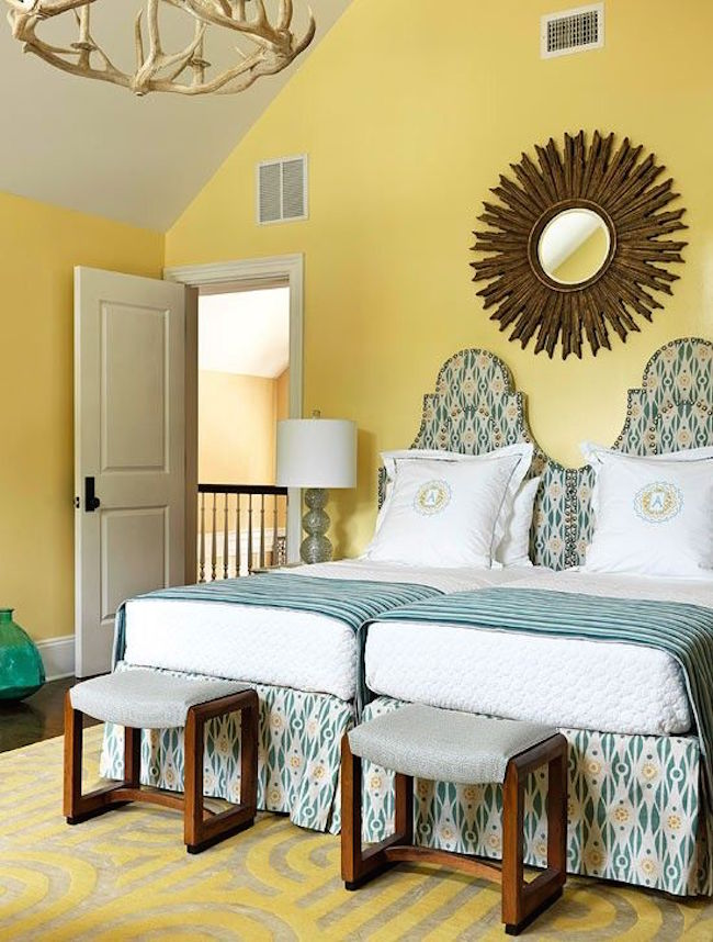Two twin beds pushed together in yellow room