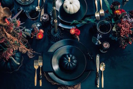 Very elegant black Halloween table setting with pumpkins and autumn foliage