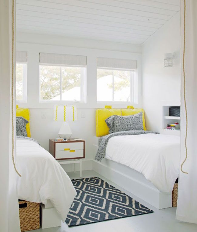 Very white guest room with bright yellow twin bed pillows