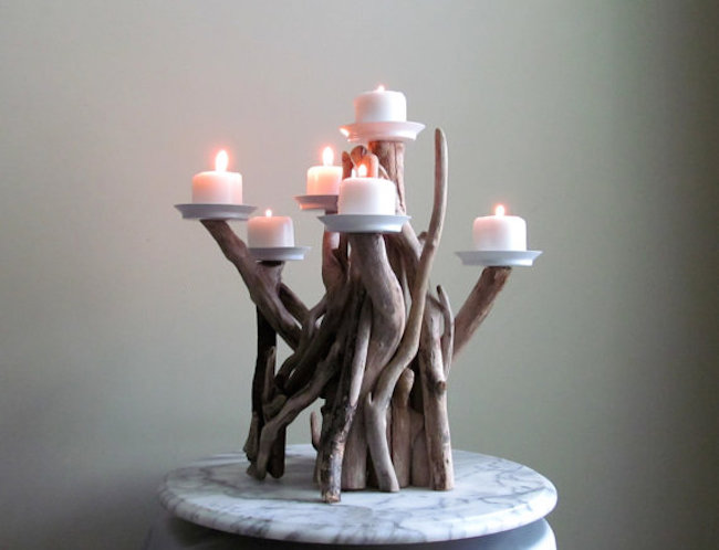 Votive candles lit on a driftwood candelabra