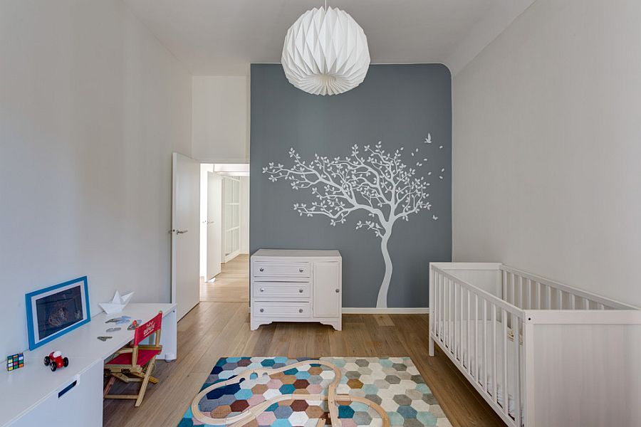 Wall mural blends into color scheme of the nursery while rug brings geometric class