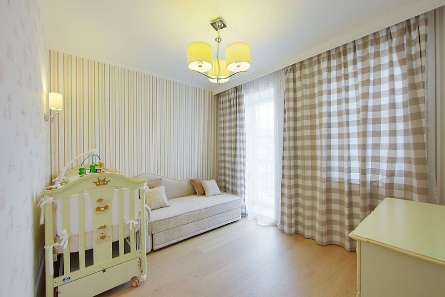 Wallpaper and drapes bring subtle pattern to the cozy nursery