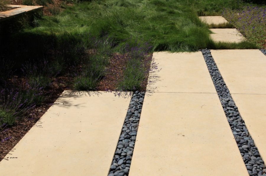 Weed barrier fabric on a garden pathway The Pros and Cons of Preventing Weeds with Landscape Fabric