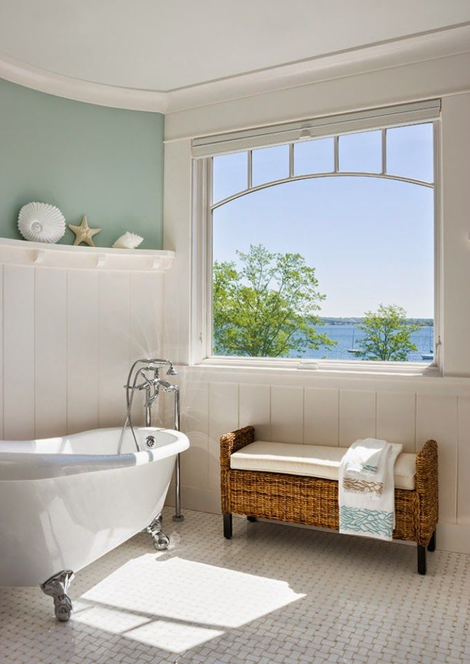 Wicker bench and cushion beneath window in white bathroom
