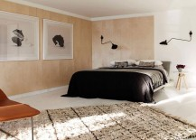 Wooden walls with large black and white framed picures in the bedroom
