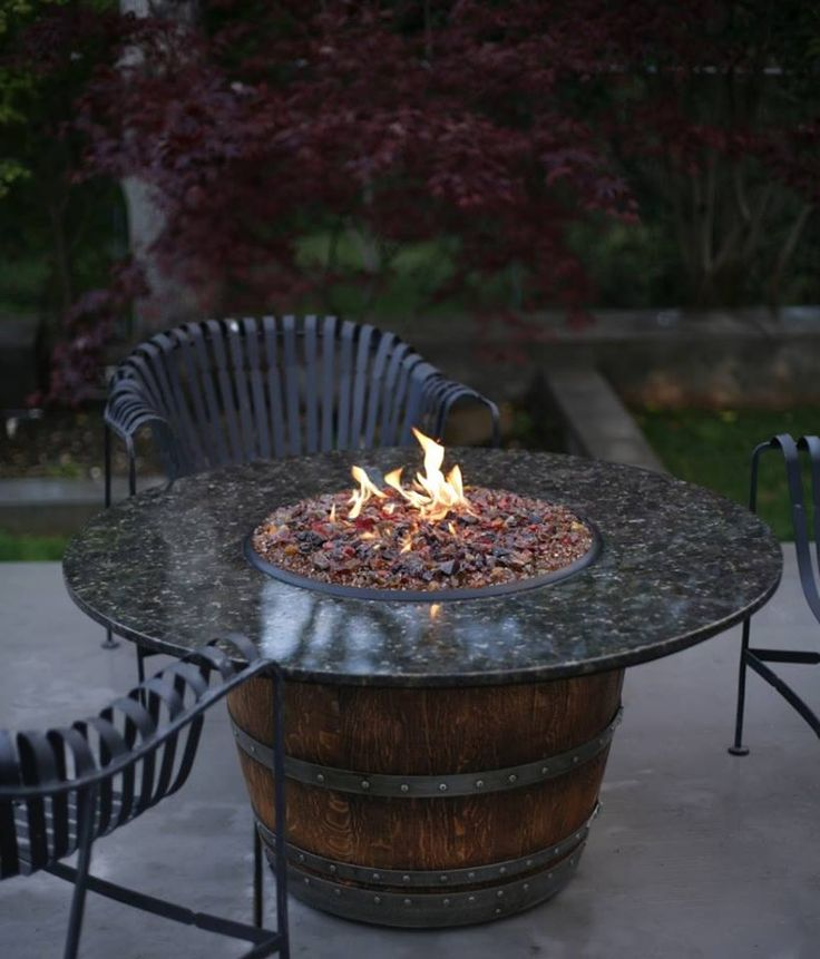 A fire burns in an old wine barrel repurposed as a fire pit
