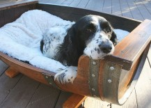 An adorable dog lounges in his wine barrel bed 217x155 8 Stunning Uses for Old Wine Barrels