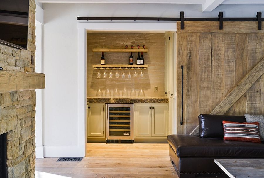Barn door leads to the small home bar in the living room [Design: Landmark Construction]