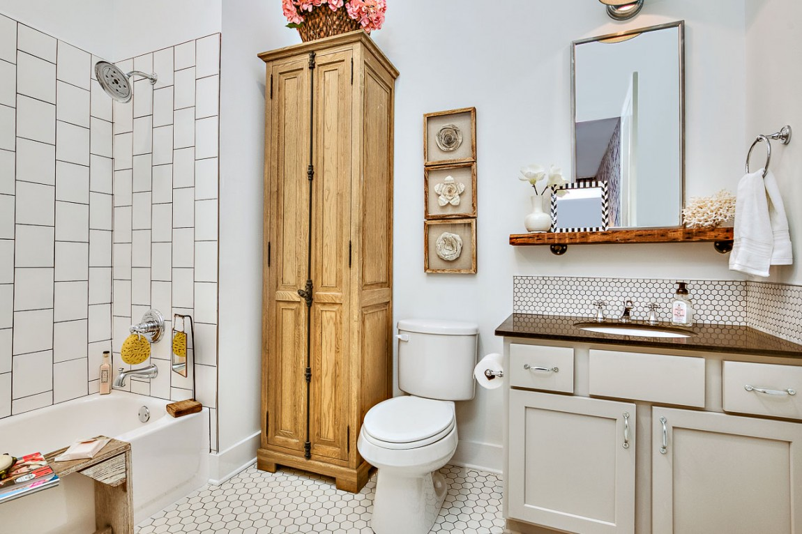 Bathroom in white with penny tiled flooring and wooden cabinet