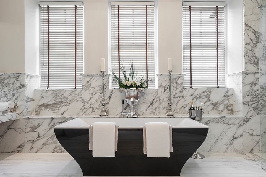 Beautiful contemporary bathtub in black set against a marble backdrop [Design: Alexander James Interiors]