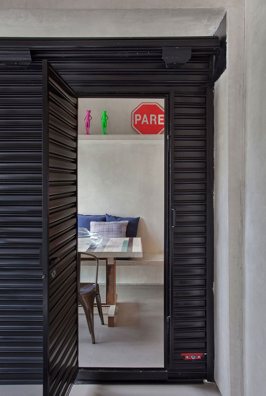 Black metal rolling partition creates the guest space