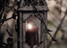 Black weathered lantern with candle hanging from tree