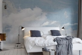 Blue and white cloud wallpaper behind a bed