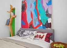 Bookcase, pillows and wall art add color to the white bedroom