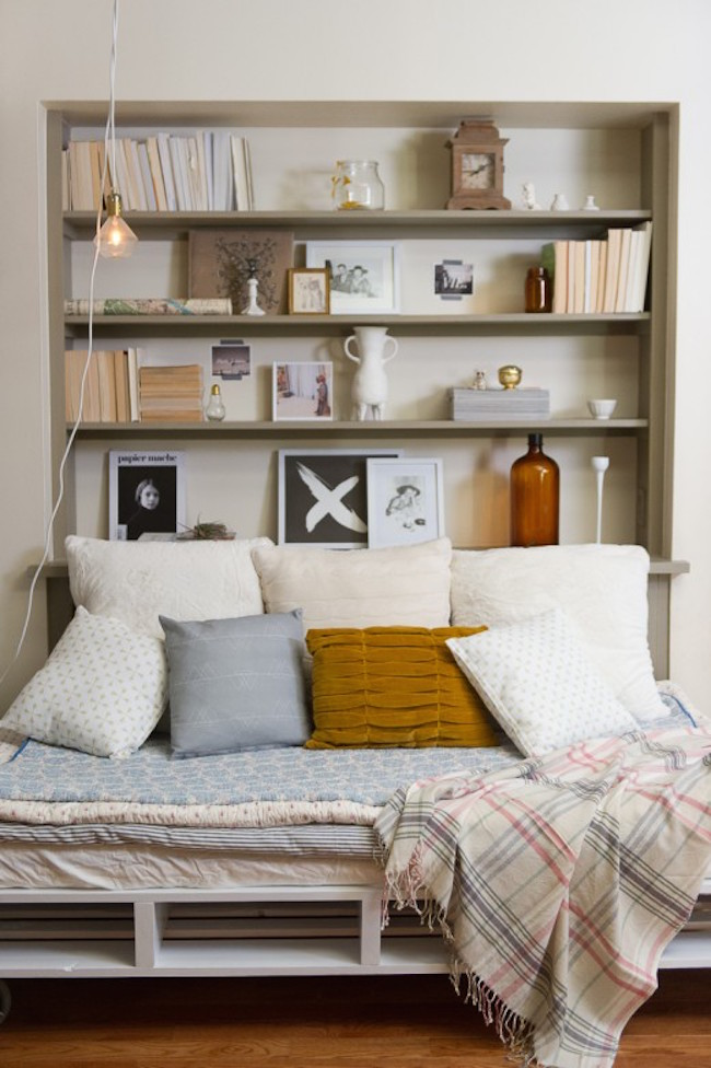Bookshelf with bed positioned up against it from one side