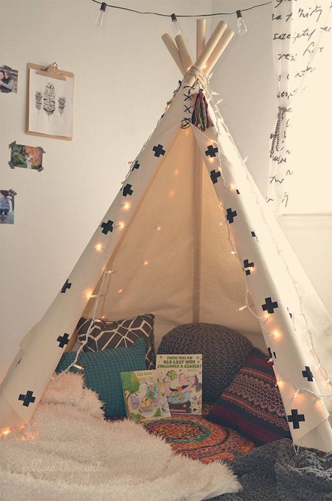 Simple teepee stocked with pillows and books