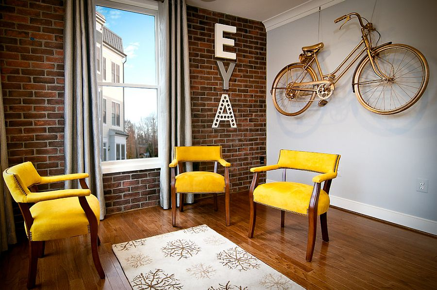 Compact living room with brick wall and pops of yellow and gold [Design: The Neighborhoods of EYA]