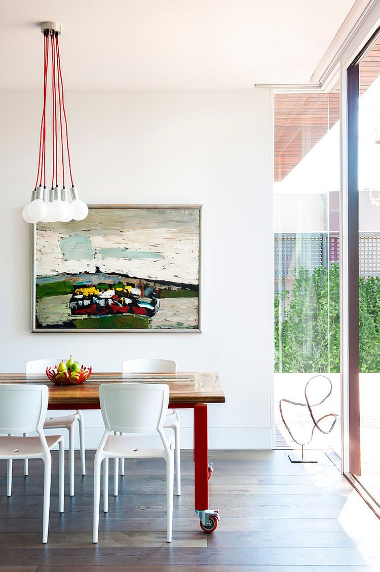 Contemporary dining room in white with lovely use of red accents