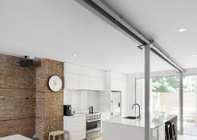 Contemporary kitchen of the home sits next to the exposed brick wall 217x155 Sensible Styling: Breezy Remodel of Apartment Set in 1920s Building