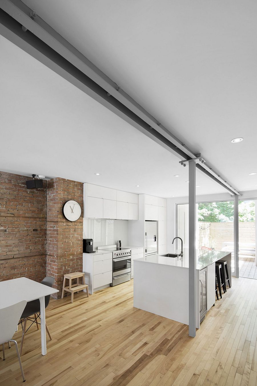 Contemporary kitchen of the home sits next to the exposed brick wall
