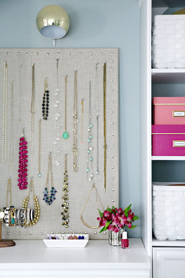 Cork board jewelry organizer using linen fabric and thumbtacks for a nailhead border