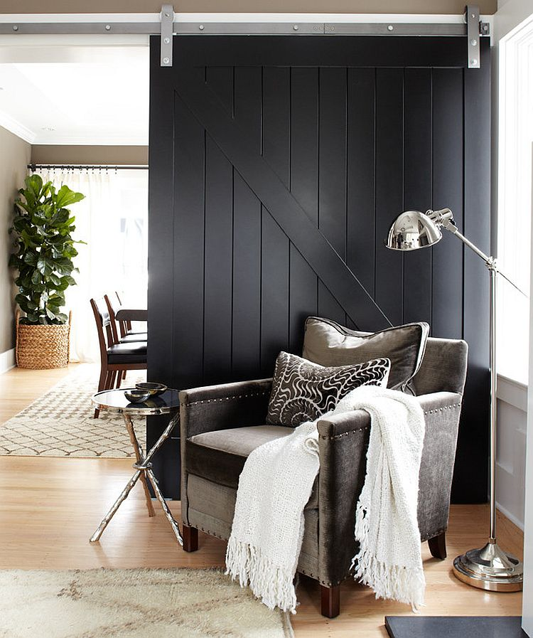 Dark black barn door fits in with the contemporary theme of the living room seamlessly [Design: Urrutia Design]