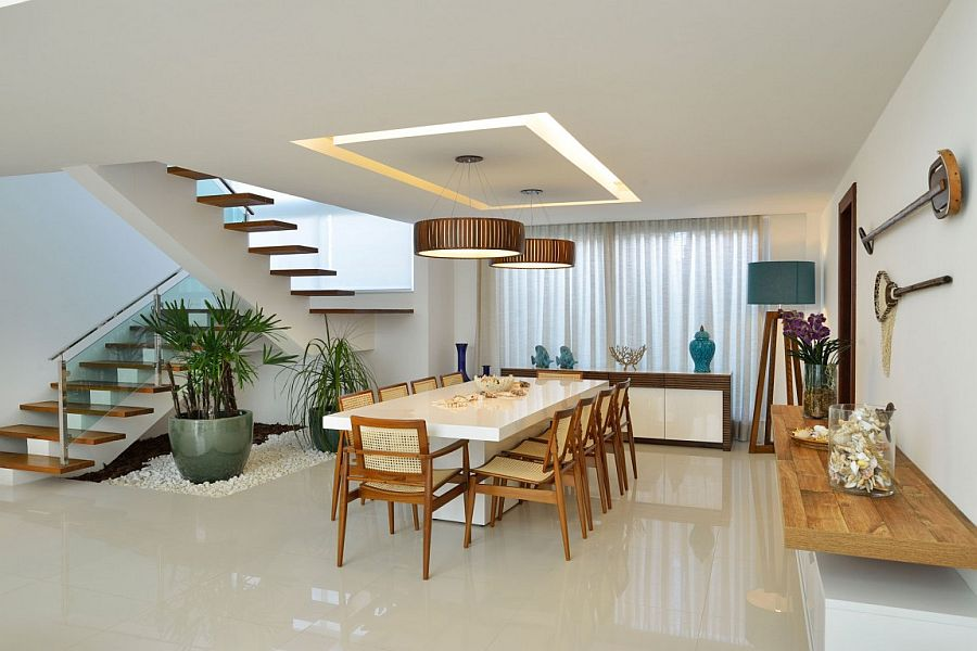Dining room with sleek floating shelf, oversized floor lamp and brilliant pendant lighting