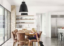 Dining space with open shelves in wood, large pendants and a wooden dining table