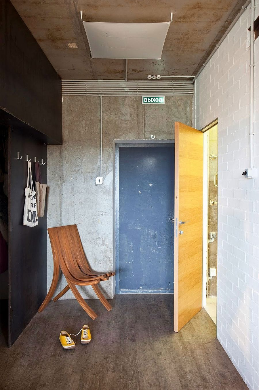 Entrance of the small Russian apartment with exposed concrete and tile walls