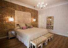 Exposed brick wall and glamorous lighting in the chic bedroom [Design: Pia Capdevila]