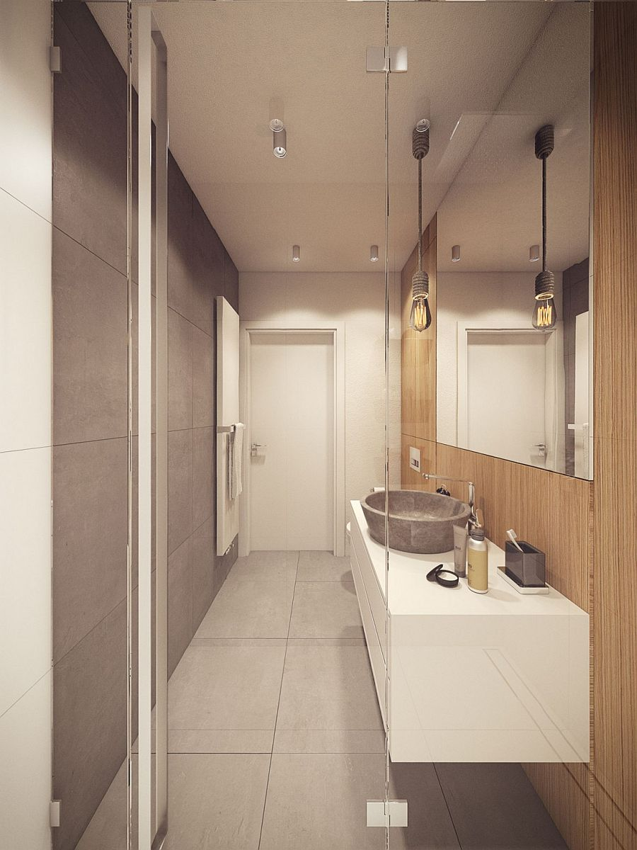 Exposed concrete surfaces and edison bulb lighting create a cool bathroom