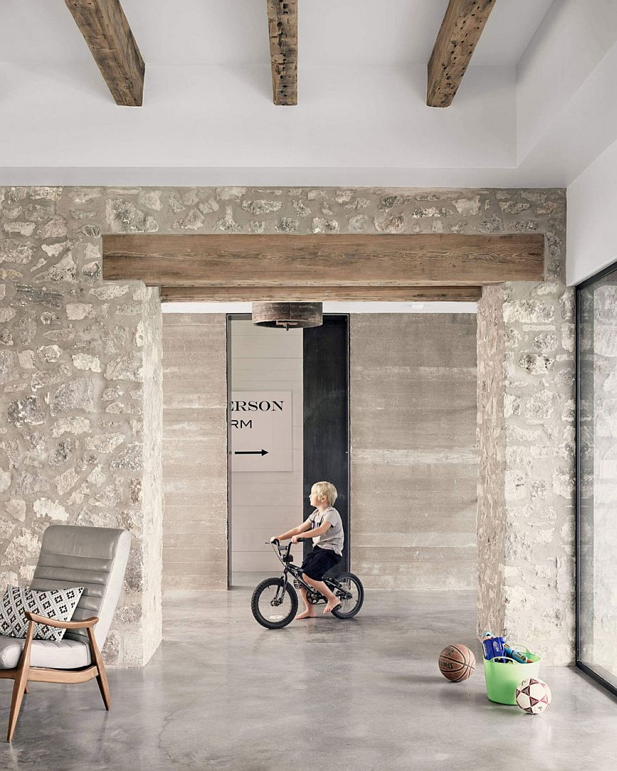 Exposed wooden beams and stone walls shape the interior of the modern home