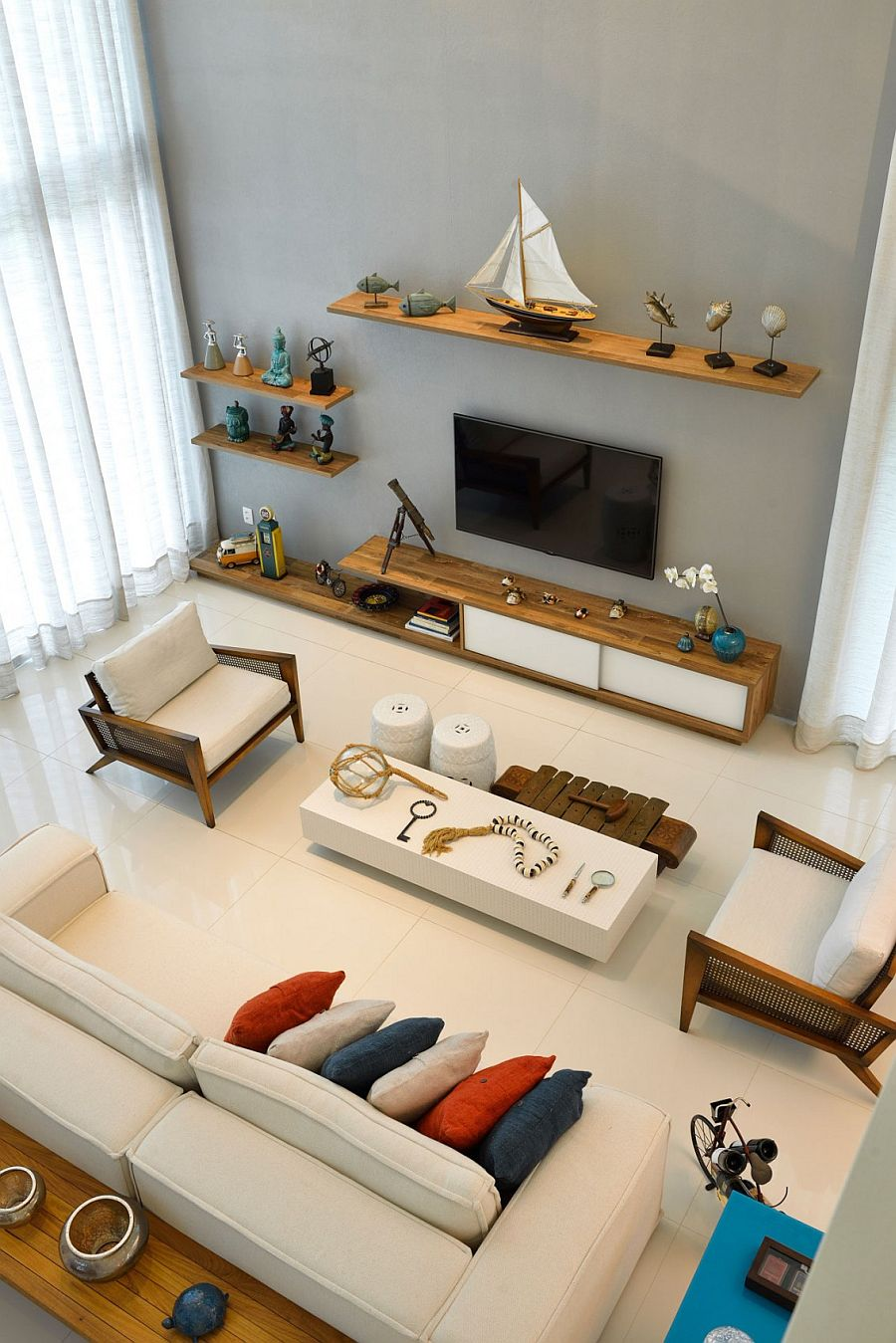 Floating wooden shelves in the living room with nautical themed decoration