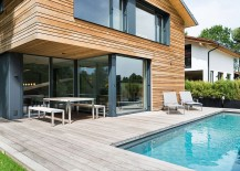 Glass doors connect the living area with the wooden deck and pool outside