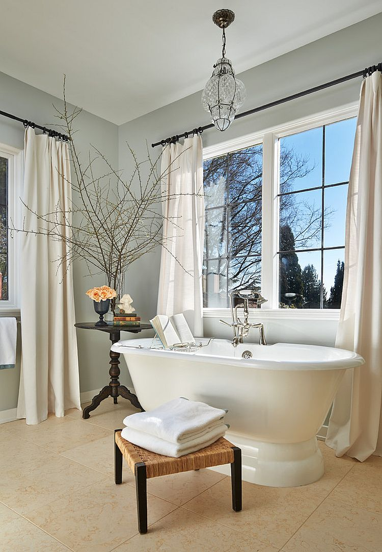 Gray and white bathroom with classic freestanding bathtub, footstool and side table [Design: Janof Architecture]