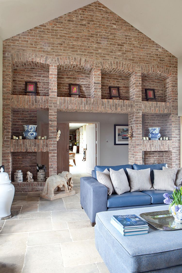 Imposing brick walls and shelves set the tone in this living room [Design: Carolyn Parker Interior Design]
