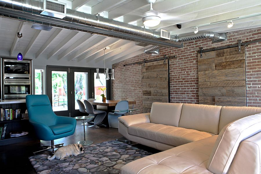 Industrial living room with brick wall and sliding barn doors [Design: The Ranch Mine]