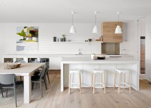 Kitchen and dining area of the Aussie beach house with a neutral color scheme and lovely wall art