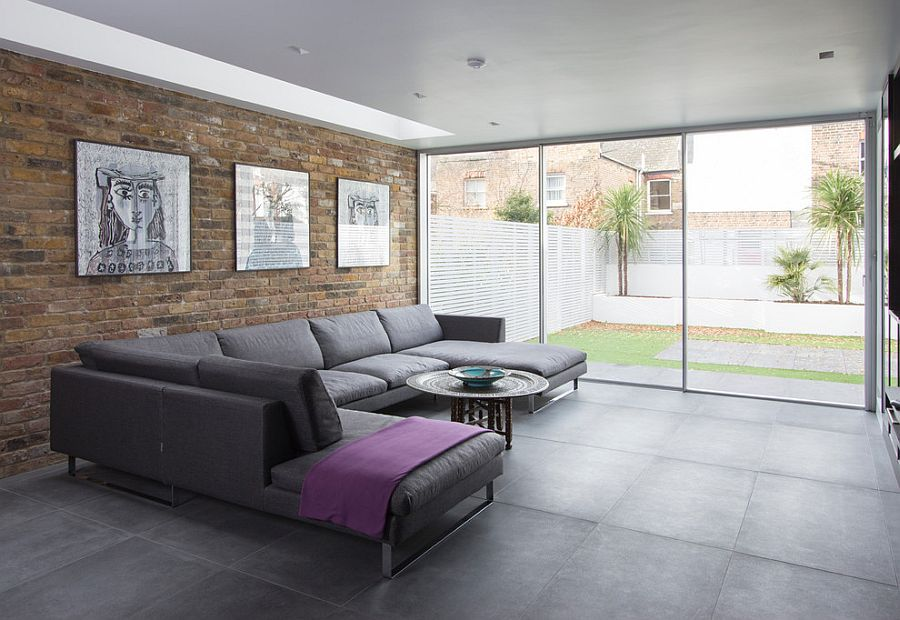 Large gray couch, brick and glass walls create a lovely contemporary living room [From: IQ Glass UK]