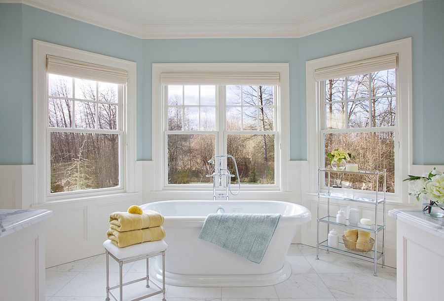 Light blue and white bathroom with sleek stool next to the bathtub [Design: Garrison Hullinger Interior Design]