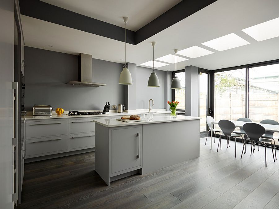 Lighting and flooring create a fusion between the various shades of gray in the kitchen [Design: Harvey Jones Kitchens]