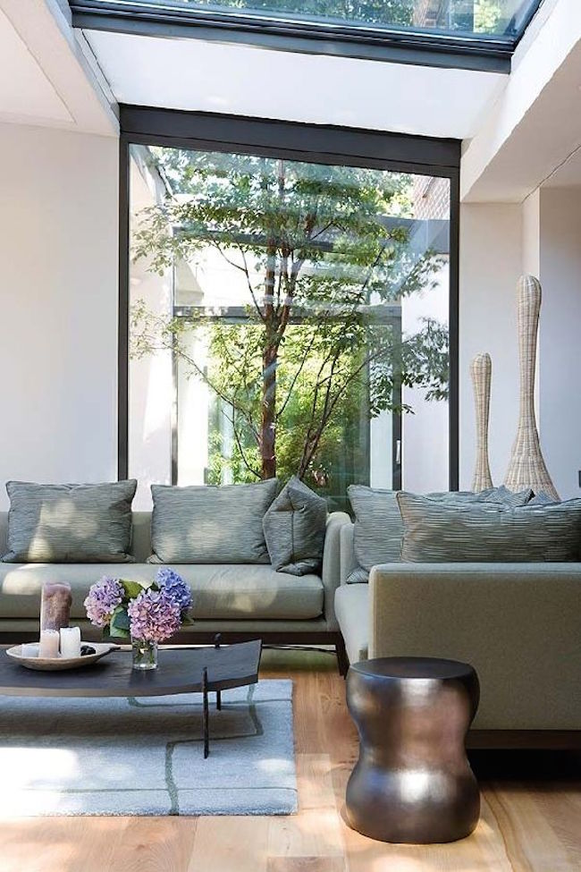 Living room that looks in on a gorgeous green courtyard