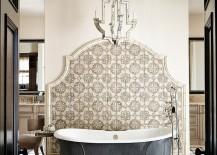 Mediterranean bathroom with pewter bathtub backed and an elegant tile wall