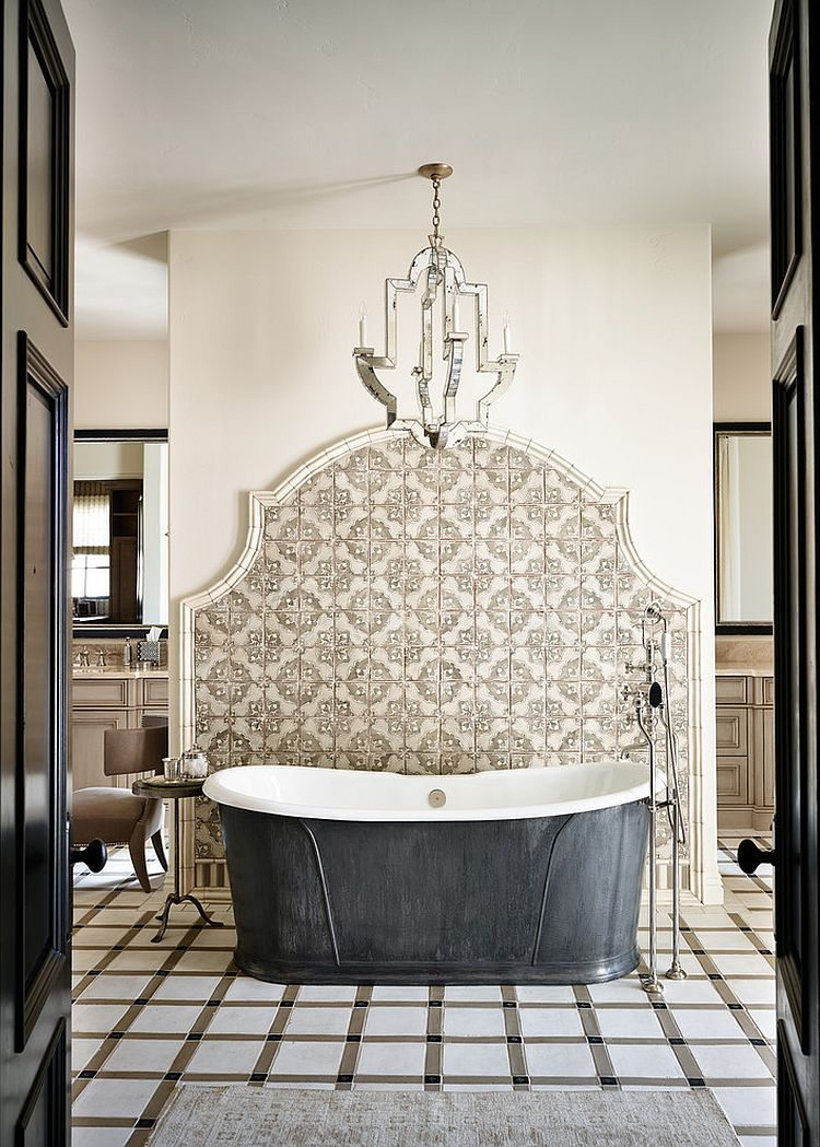 Mediterranean bathroom with pewter bathtub backed and an elegant tile wall [Design: Wiseman & Gale Interiors]