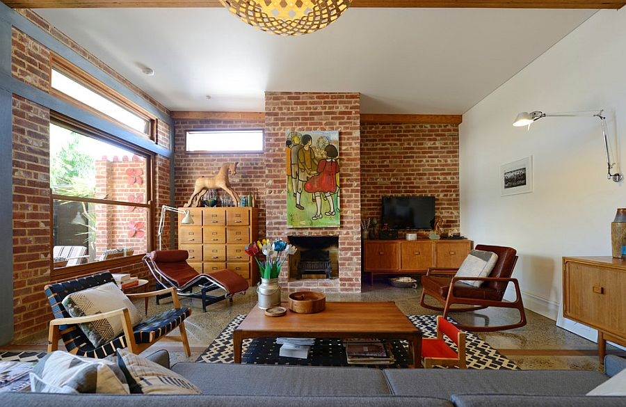 Midcentury living room with brick walls and oversized artwork above fireplace [From: Jeni Lee]