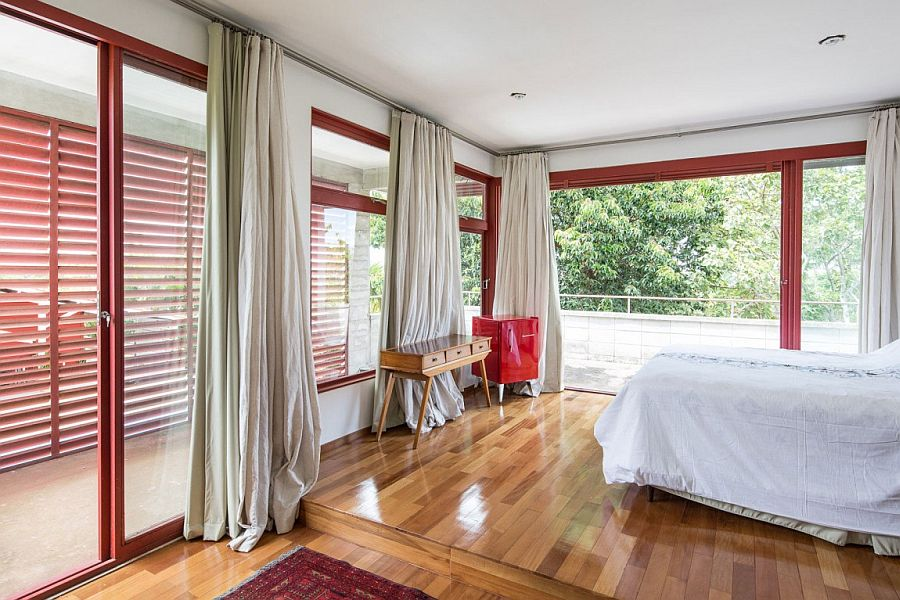 Modern bedroom with white drapes, glass doors with red metallic frames and polished wooden flooring