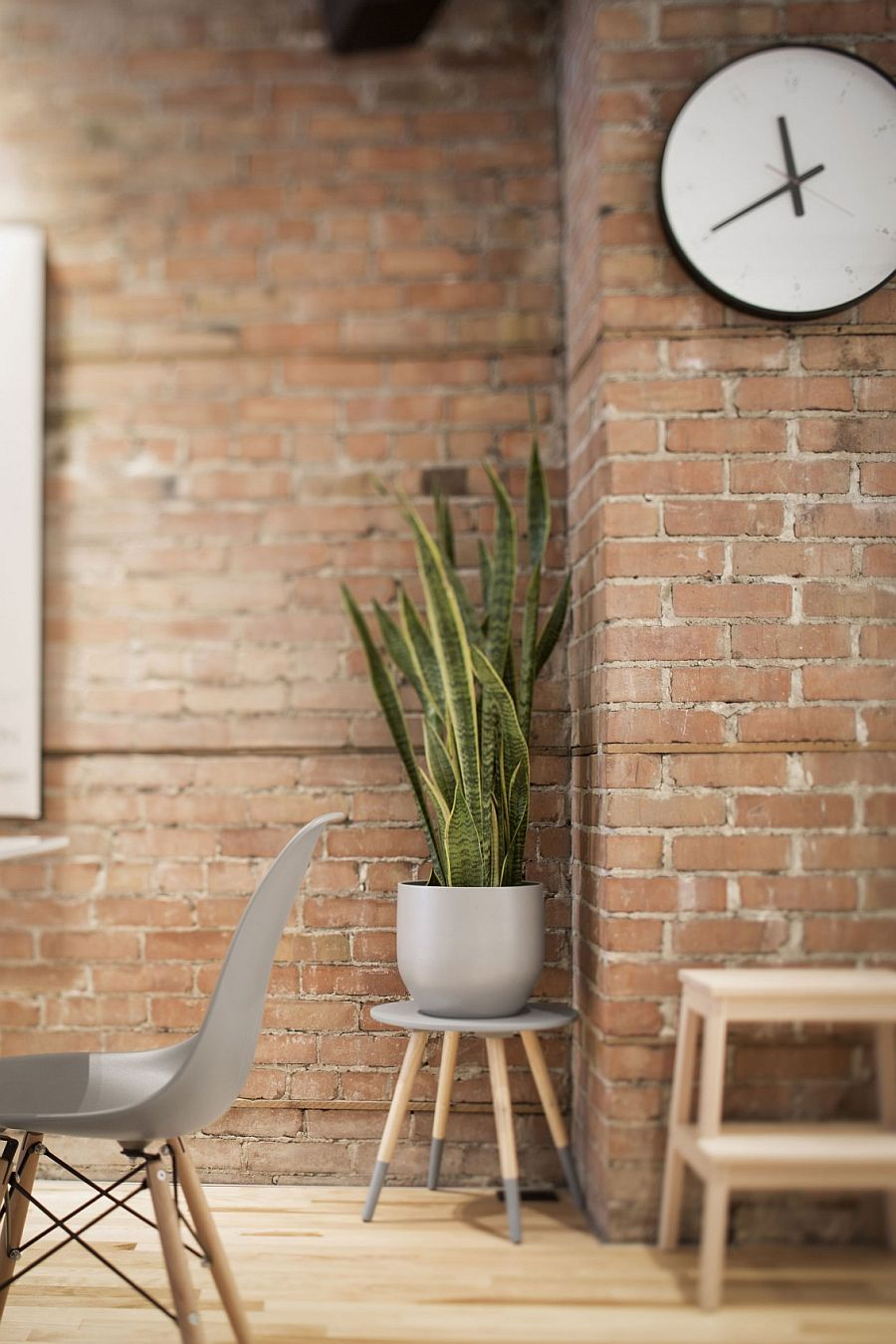 Modern decor sits in the living room with brick wall background