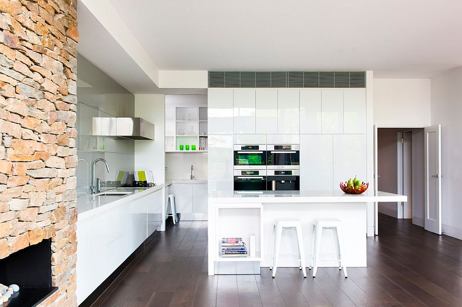 Modern kitchen in white with stone wall fireplace and