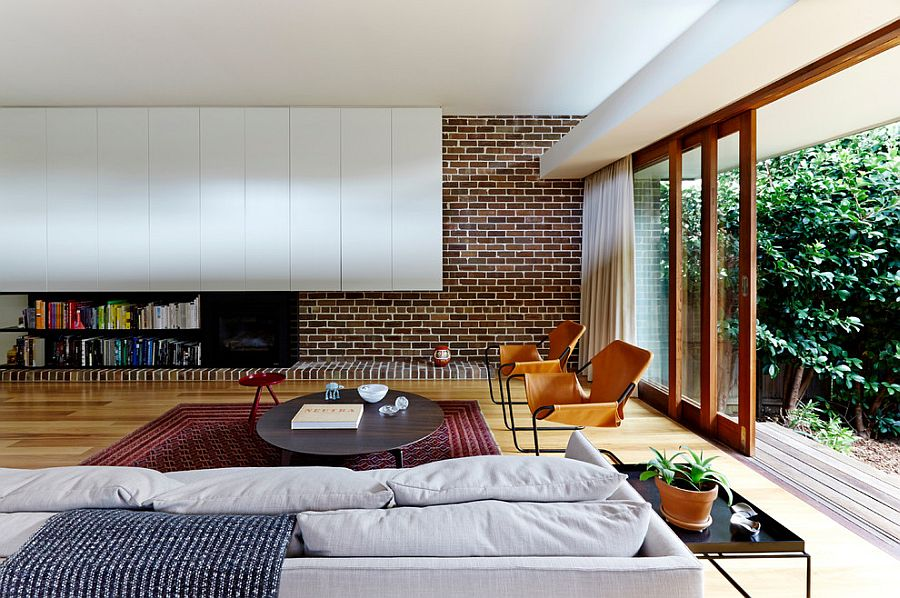 Modern living room mixes brick wall with contemporary shelves in white